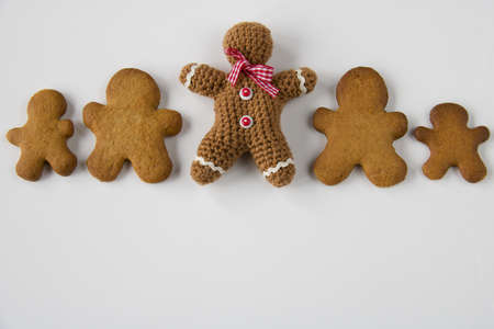 row of gingerbread man near a gingerbread crocheted, copy space