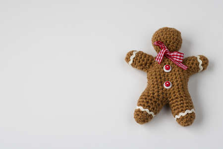 homemade wool gingerbread man crocheted, white background, copy space