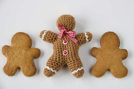 close up of gingerbread man crocheted and two biscuits, copy space