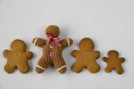 different gingerbread men in pastry and crocheted, isolated on white, copy space