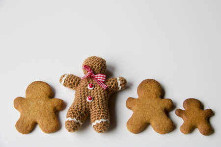 wool gingerbread man handmade chrochet near some gingerbread biscuits, copy space Stock Photo