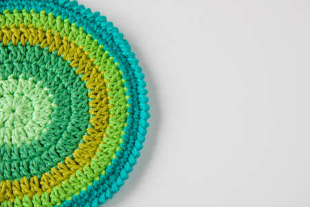 close up of handmade crochet pot holder in green shades, copy space