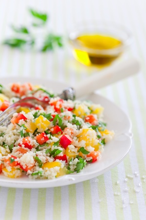 Couscous salad with sweet peppers and herbs, selective focus