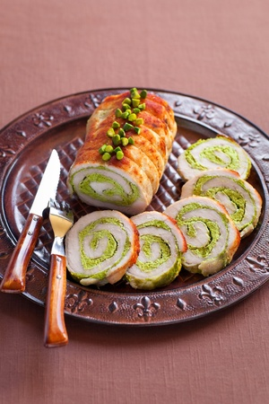Roasted pork roulade with pistachio on plate photo