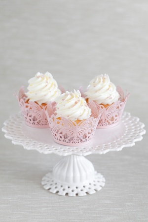 Cupcakes with a swirl of vanilla buttercream frosting and pink decor on cake stands photo