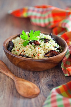 Bulgur, dried plum, chili, parsley salad in wooden bowl on the table, selective focus photo