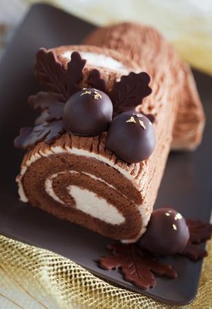 Traditionele kerstmarkt Yule Log taart versierd met chocolade kastanjes, selectieve aandacht Stockfoto