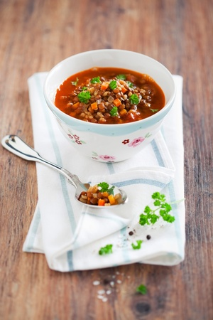 Brown lentil soup in a bowl on the table, selective focus photo