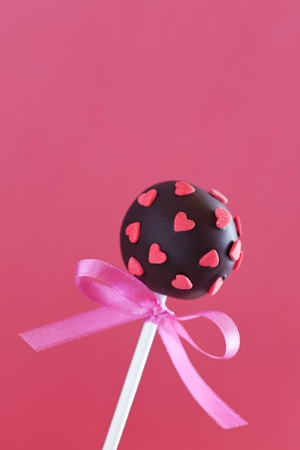 Chocolate cake pop decorated with pink sugar hearts  photo
