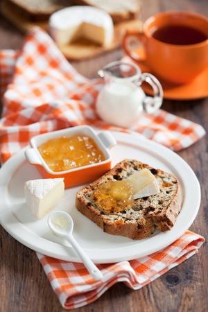 bread soda: Grain Irish soda bread slice, brie cheese and jam on plate, selective focus