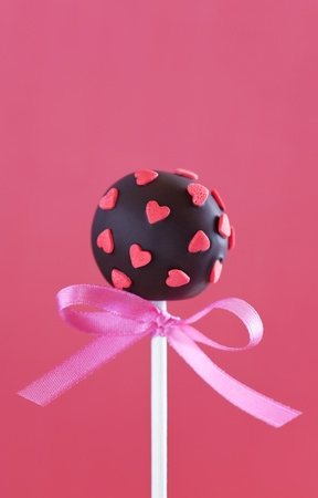 Chocolate cake pop decorated with pink sugar hearts, selective focus  photo