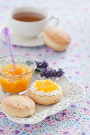 Orange scones with lavender, served with fresh cheese and orange jam, selective focus