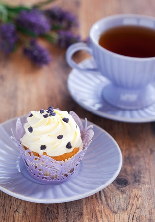 Lavender cupcake decorated with lavender sugar and cup of hot tea, selective focus  photo