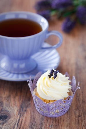 Cupcake with lavender sugar and cup of hot tea, selective focus Archivio Fotografico