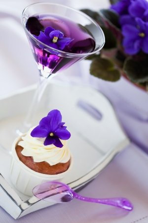 Cupcake decorated with whipped cream and violet flowers and cocktail, selective focus Stock Photo