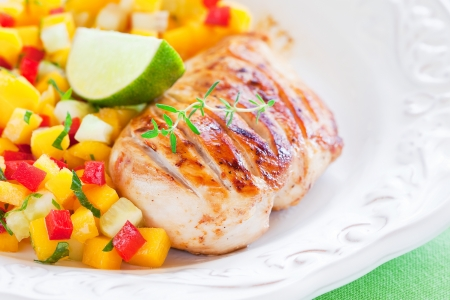 Grilled chicken fillet and mango, cucumber, pepper salsa. Selective focus.