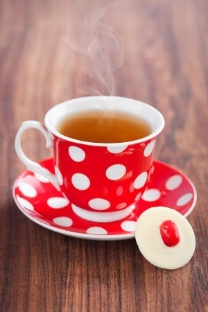 Cup of hot tea and white chocolate cranberries candy, selective focus  photo