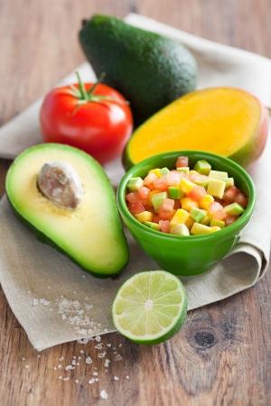 Avocado tomato mango salad with lime dressing, selective focus