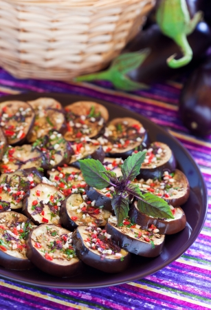 Grilled aubergine salad with garlic, chilli, basil and parsley dressing. Selective focus.