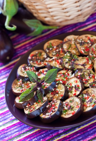 Grilled aubergine salad with garlic, chilli, basil and parsley dressing. Selective focus photo