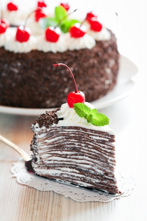 Piece of chocolate crepe cake with whipped cream and glazed cherries, selective focus  photo