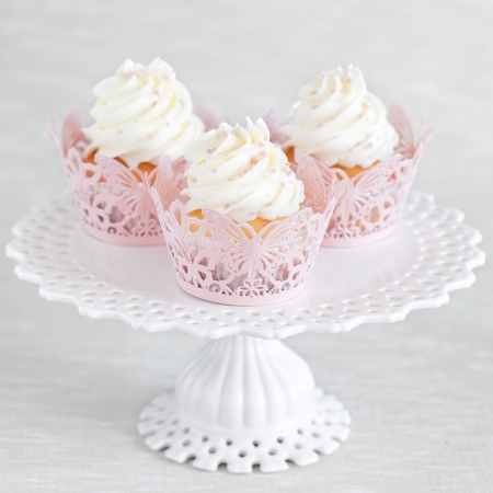 cup cakes: Cupcakes with vanilla cream on cake stand, selective focus Stock Photo