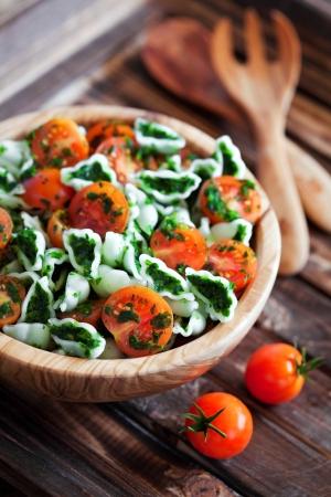Cherrytomaatjes met glutenvrije pasta en spinazie saus, selectieve aandacht Stockfoto