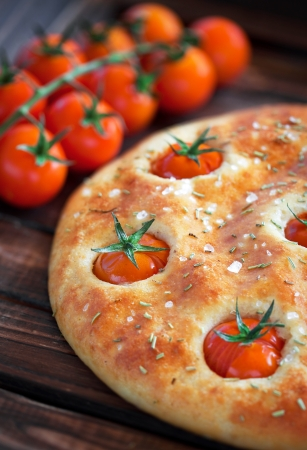 Focaccia with cherry tomatoes, rosemary and sea salt, selective focus photo