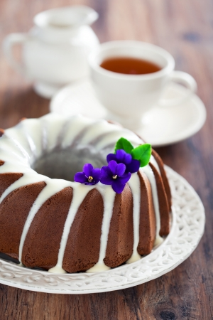 Chocolate bundt cake with icing, selective focus photo