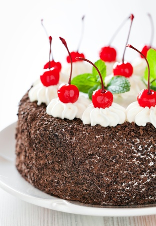 Chocolate cake with whipped cream and glazed cherries, selective focus photo