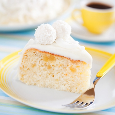 Slice cake with pineapple and white chocolate decorated coconut truffles, selective focus