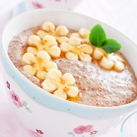 Oatmeal porridge with banana and flax seed, selective focus photo