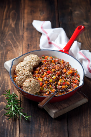 cast iron red: Red rice with vegetables and vegan tofu flax seeds cutlets in cast iron skillet, selective focus
