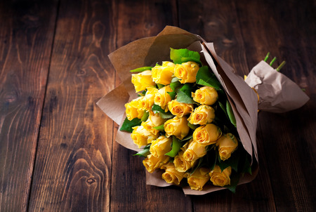 Yellow roses bouquet in kraft paper on a wooden background, selective focus 스톡 콘텐츠