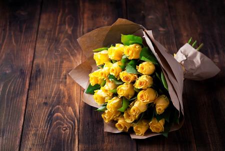yellow roses: rosas de color amarillo ramo en papel kraft sobre un fondo de madera, enfoque selectivo Foto de archivo