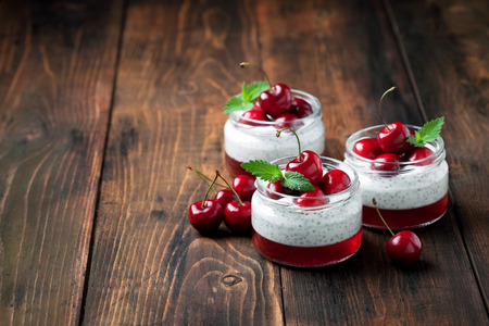 Chia seeds yogurt pudding, jelly and fresh sweet cherries in jar, selective focus Stock Photo