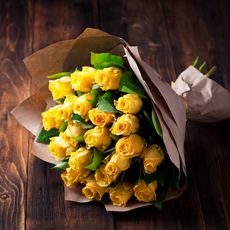 Yellow roses bouquet in kraft paper on a wooden background, selective focus Stock Photo