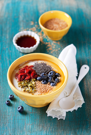 flax seeds: Healthy breakfast yogurt bowl with chia seeds, flax seeds, goji berries, blueberries, pistachio and maple syrup, selective focus