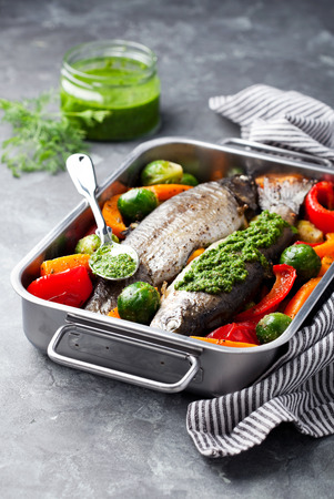 the concrete: Baked trout with vegetables and dill pesto, selective focus