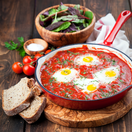 cast iron pan: Shakshuka with tomatoes and eggs in a cast iron pan, selective focus Stock Photo