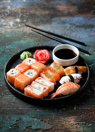 Sushi set nigiri and rolls served in round plate, selective focus