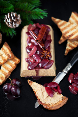 Pate with grapes in wine sauce with spices and toast, selective focus