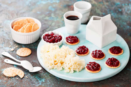 Cheese Tete de Moine with crackers and cranberry jam, selective focus