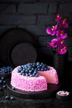 Homemade crepe cake with pink coconut pitahaya cream and fresh blueberries on a black background, selective focus