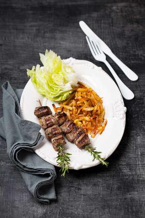 Grilled lamb kebabs on rosemary skewers, fried parsnips and Iceberg lettuce, selective focus