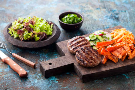 Grilled burger cutlets with baked sweet potato, vegetables and salad served on wood chopping board, selective focus
