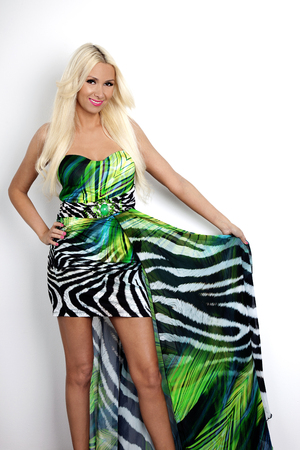 The Beautiful, Happy, Blond woman is smiling. Holding the colorful dress