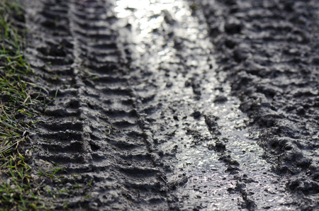 persecution: tire tracks in the mud Stock Photo