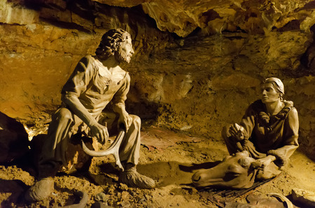 statues of prehistoric humans in cave