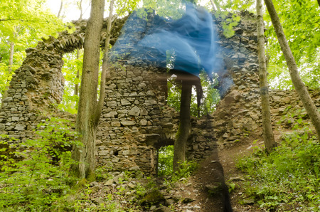 ghost rock: Blurred tourists before the castle ruins in the forest